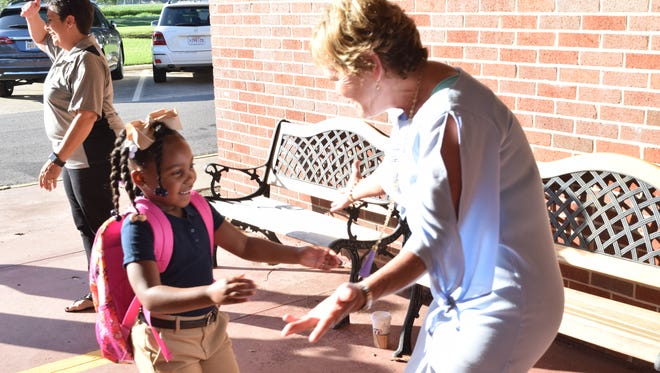 Cherokee Elementary School principal Bonnie Lord (right) welcomes Malaina Rhone, a first-grader, back to the school with a hug. Staff and faculty greet students on the first day of school Tuesday, Aug. 15, 2017.