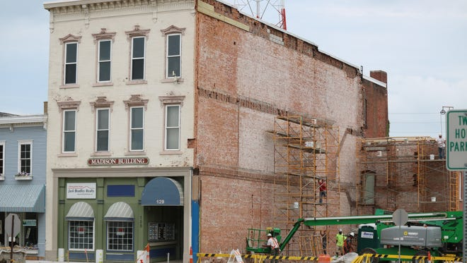 Demolition work continues at 131 Madison Street while crews restore the adjoining buildings' exterior walls.
