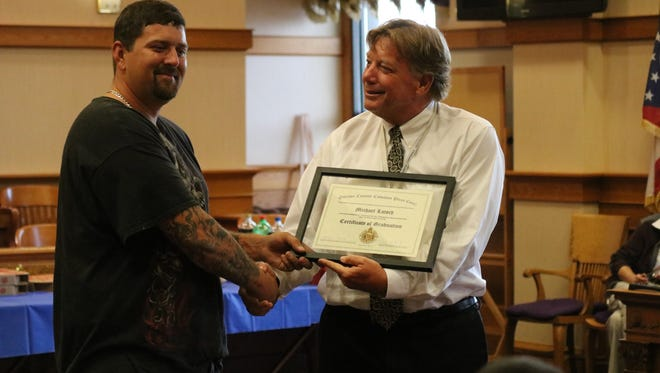 Michael Latsch, left, is presented with a certificate by Ottawa County Common Pleas Court Judge Bruce Winters after graduating from the DATA program, or Drug Court.