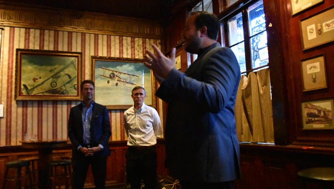 State Rep. Frank White, center, and Pensacola Mayor Ashton Hayward, left, look on as TJ Morales, an Airbnb community organizer, speaks to Pensacola property owners at Lili Marelene's pub on Friday, Aug. 25, 2017.