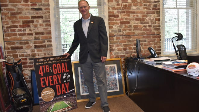 """Phil Savage, executive director of the Senior Bowl and football radio analyst on the Alabama Crimson Tide Sports Network, stands in his office in Mobile with promo poster for his book, """"4th & Goal Every Day"""" on the Nick Saban era. The book had its national release Tuesday."""