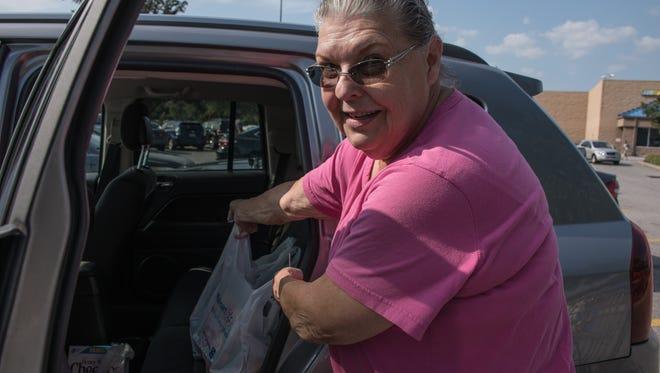 Mary Ann Callahan loads hurricane supplies into her vehicle at Walmart on Creighton Road.