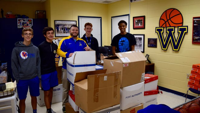 New Berlin West boys basketball coach Brandon Mattox and members of the Vikings program shipped off 58 boxes of t-shirts on Sept. 7.