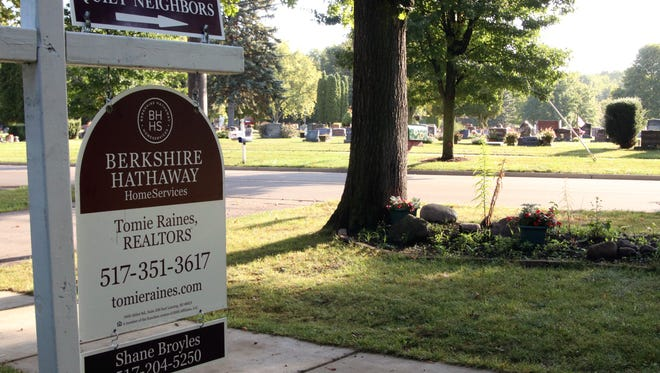 """Real estate agent Shane Broyles is using a little humor to sell a home in DeWitt that sits across the street from a cemetery. """"Quiet neighbors"""" reads the top of the """"for sale"""" sign on the property, with an arrow pointing in the cemetery's direction."""