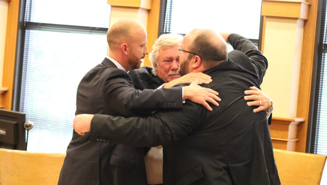 Sloopy's owner Brad Corbin, right, hugs his attorneys Kevin Zeiher, center, and Kyle Wright after being found not guilty of arson and insurance fraud in Ottawa County Common Pleas Court on Tuesday.