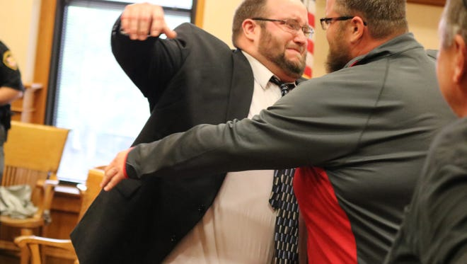 Sloopy's owner Brad Corbin, left, hugs his brother, Jeremy Corbin, after being found not guilty of arson and insurance fraud in Ottawa County Common Pleas Court.