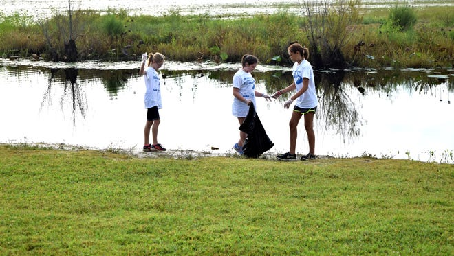 Lispeth Ann Abbott (left), Wren L'Heureux and Gabby Valdes pick up trash at Lake Jackson as part of a previous Keep Tallahassee Beautiful coastal cleanup event.