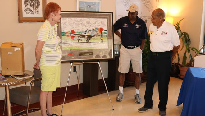 """Brad Lang, center, of the CAF Red Tail Squadron, presented Harold Brown, right, with an honorary commemorative print photo of the late Don Hinz, who is described as the original """"driving force"""" behind the organization, flying their fully-restored P-51C Mustang. Brown's wife, Marsha Bordner, is at left."""