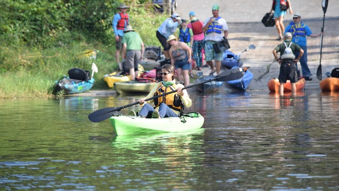 A kayaker leaves Rhoden Cove to start collecting trash from Lake Jackson on Saturday.