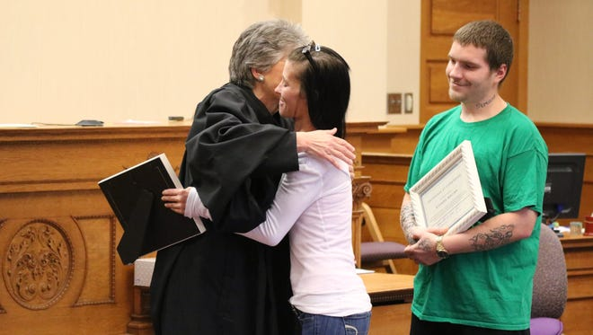 Judge Kathleen Giesler, of Ottawa County Probate and Juvenile Court, hugs Kasie Whitt and Richard Macina, who became the first couple to graduate the court's H.O.P.E. Program on Thursday.
