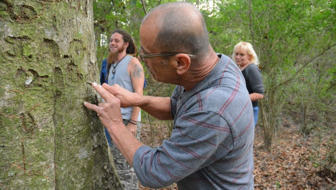 Lynyrd Skynyrd plane crash survivor Marc Frank carves into an oak tree that has served as a memorial to the plane crash that occurred on Oct. 20, 1977. Frank, who was on the plane when it went down, traveled to Amite County, Mississippi, to be a part of the 40th anniversary of the event. It was the first time he has returned to the crash site since that fateful day.
