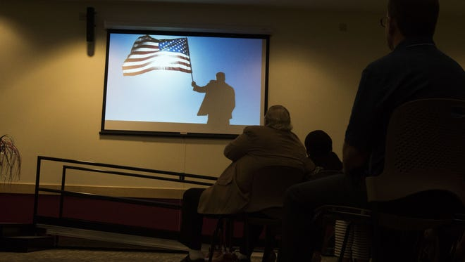 New U.S. citizens watch a video message welcoming them recorded by President Trump in Phoenix.