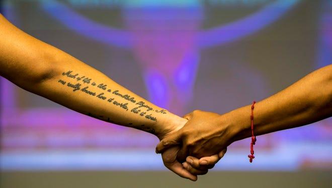 DACA recipients hold hands