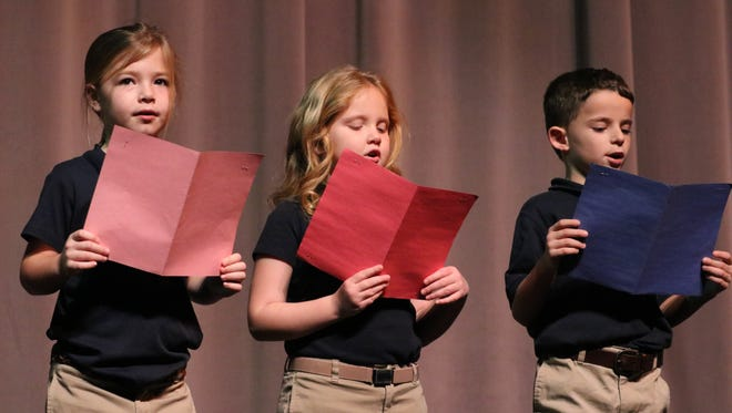 Isabella Young, Sarah Peak, Gage Wozencraft sing Christmas songs at the opening of the program.