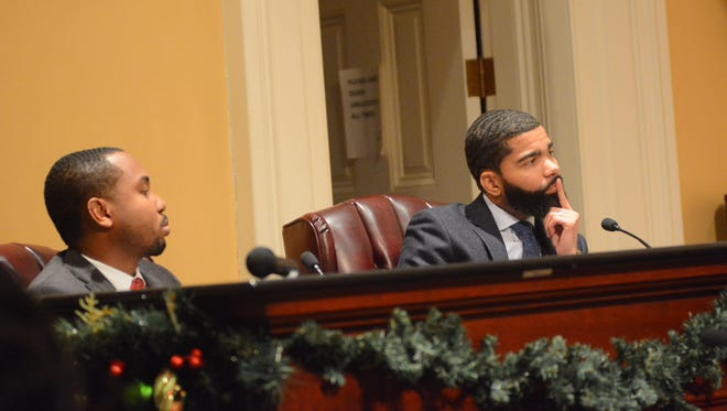 Mayor Chokwe Antar Lumumba and the City of Jackson's lobbyist, Quincy Mukoro (left), present a list of legislative priorities to the City Council Monday night.