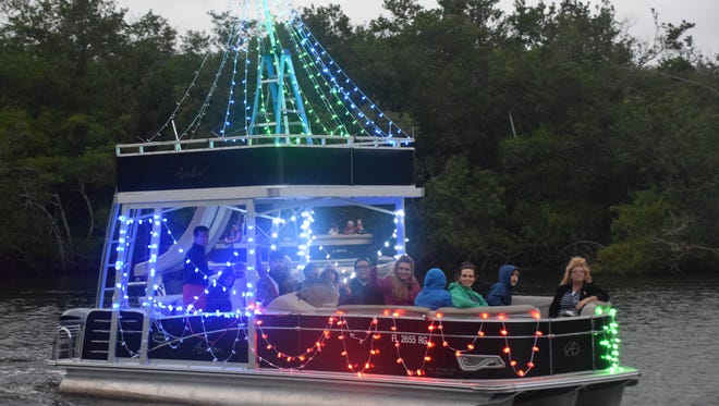 Boats packed with people lights meander up the Imperial River during the annual parade.