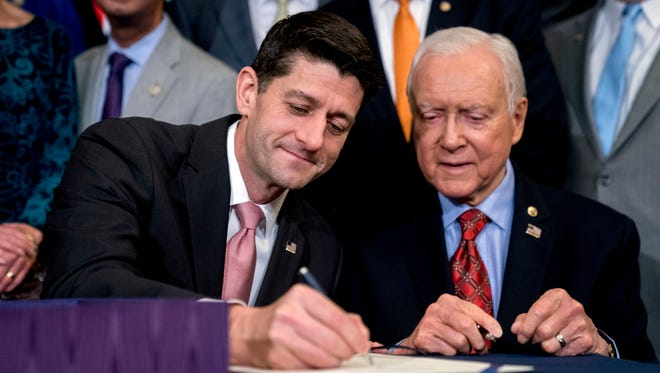 Speaker of the House Paul Ryan, R-Wis., center, accompanied by Senate Finance Committee Chairman Orrin Hatch, R-Utah, right, signs the final version of the GOP tax bill during an enrollment ceremony at the Capitol in Washington, Thursday, Dec. 21, 2017. (AP Photo/Andrew Harnik)