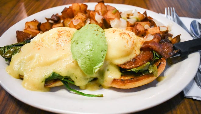 The popular eggs benedict with avocado, spinach  and jalapeno bacon at Deja Vu.