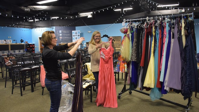 Night to Shine Prom volunteers Charlene Pyeatt, left, and Jaina Watson sort and organize donated dresses on Friday, Jan. 5, 2018, at Community Life United Methodist Church in Gulf Breeze. Pyeatt and Watson are getting the dresses ready for prom guests to try on at two boutique nights later this month at the church.