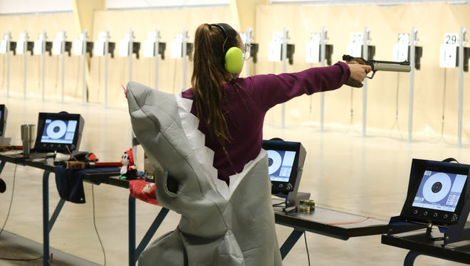 Violetta Ziborov takes aim while donning a shark costume at the Camp Perry Open's popular Super Final event on Saturday.