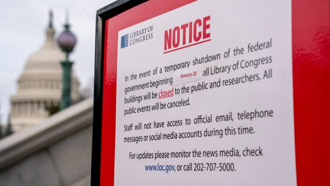 The dome of the Capitol Building is visible behind a closure sign that is posted outside of the Library of Congress in Washington, Monday, Jan. 22, 2018. The federal government shut down Friday, halting all but essential operations.