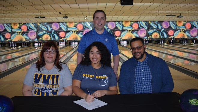 Alyanna Brown, seated center, is flanked by her mother, Cathy Johnson, left, and her junior league coach at Suburban Bowlerama, Joel Logan, right. In the rear is Terry Miller, proprietor of Suburban Bowlerama. SUBMITTED