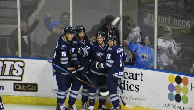The Ice Flyers' Shayne Morrissey (12), who produced two goals, two assists, joins with teammates after a goal celebration during Pensacola's 9-5 win Friday night against the Evansville Thunderbolts.