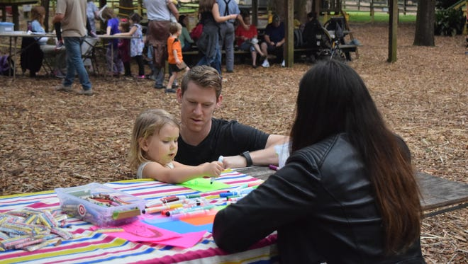 Emma Mills, 3, draws with the help of her dad Dustin at the LeMoyne Center for Visual Arts creation station at the Matinee of the Arts on Saturday Feb. 10 at the Tallahassee Museum. The family came to the event because it was free and looked like fun.