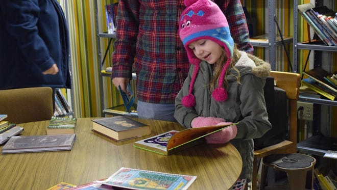 Aubrey Monahan of Upper Deerfield checks out one of the countless children's books offered at the Friends of the Millville Library basement book sale on Saturday, Feb. 10. Photo/Jodi Streahle