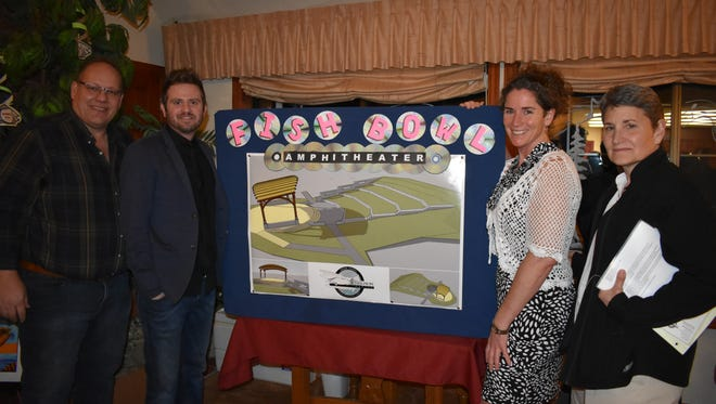 From left, local business owner Brian Petersen, architect Anthony Alan Krueger, Hood Canal Salmon Enhancement Group Executive Director Mendy Harlow and project manager Jeanne McCann stand with a conceptual design of the planned Fish Bowl Amphitheater at the Salmon Center. The amphitheater would feature outdoor concerts and movies.