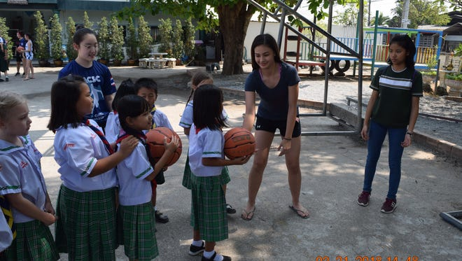 St. Paul Christian Warriors Monica Giger helps students play a game during the Warriors' visit to the School of Promise in Chiang Mai, Thailand.  Giger and her teammates participated in a service mission at the school during the 2018 Asian Christian Schools' Conference Girls' Basketball Tournament.