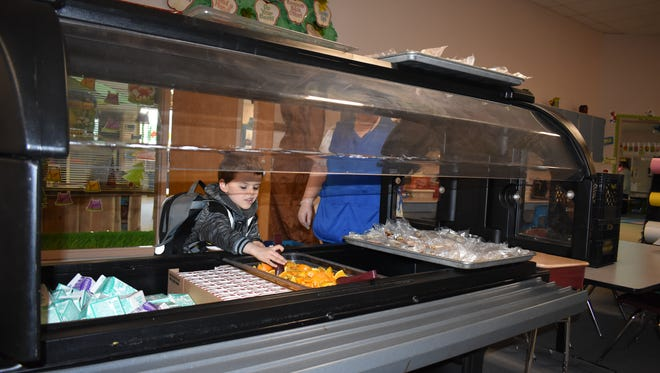 Kindergarten student Wyatt Shook reaches for an orange at the salad bar during breakfast at Sand Hill Elementary. North Mason School District was able to purchase new salad bars, new ovens and new portable hot boxes for Belfair and Sand Hill elementaries with grant funding last year.