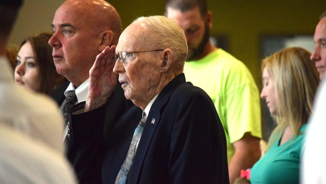 Army Staff Sgt. W. Richard Wynn (center) salutes the flag during the singing of the national anthem during a BIg Bend Hospice Valor Ceremony honoring his time spent in WWII on March 17.