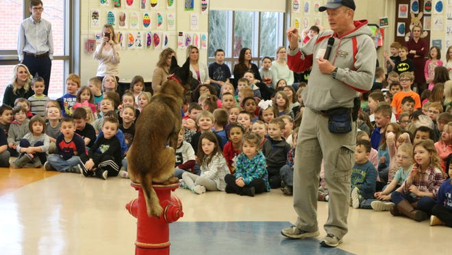 Mya, a 5-year-old Belgian Malinois from the Erie Shores K-9 Academy, performs with owner and trainer Marty Mortus during a visit to Bataan Primary School on Wednesday.