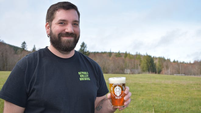 Evan Puckett holds up a cold glass of the Keyhole Farmhouse Ale, a saison that gets its flavor from French yeast. Puckett co-owns Keyhole Valley Brewing, which he operates out of his garage at Keyhole Valley Ranch in Shelton.