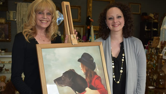 """From left, photographers Jeannie Scanlon and Feather Meredith stand with Meredith's photo, """"A Girl and Her Dog,"""" which won first place in a fine art contest sponsored by Rangefinder Magazine. Meredith digitally alters photographs to create dreamlike works of art."""