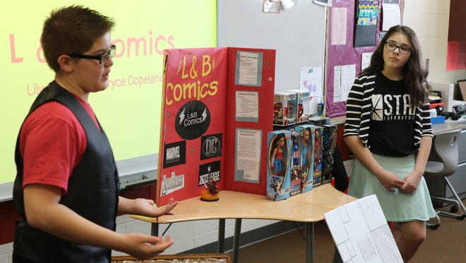 """Bryce Copeland and Lily Lucero present their business idea, L&B Comics, at Port Clinton Middle School's Young Entrepreneurs """"Shark Tank"""" event."""