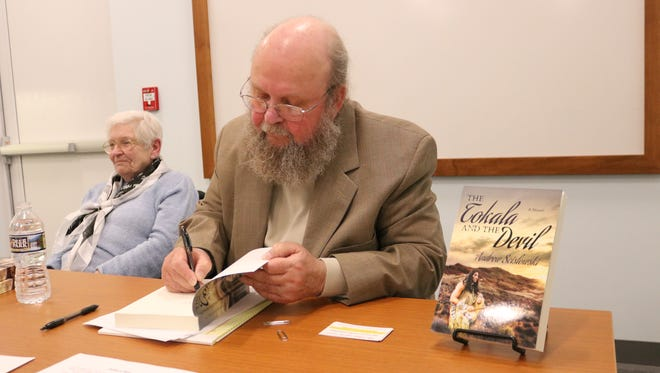 """Andrew Scislowski signs a copy of his book """"The Tokala and the Devil"""" during an event at the Marblehead Peninsula Branch Library."""
