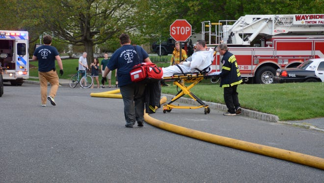 Kevin Carcich, 46, is wheeled on an ambulance stretcher from his burning home on Yale Court in Tinton Falls, after suffering burns and smoke inhalation in the Friday evening blaze on May 4, 2018.