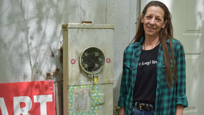 Colleen Walls stands outside of her empty meter box at her home in Belfair. Walls refused Mason County Public Utility District No. 3's advanced digital meters and the digital non-transmitting meters.