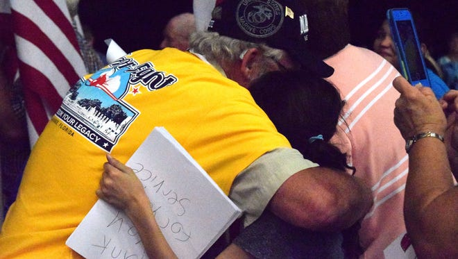 Cpl. Daniel Schilling (left) hugs 11-year-old Abbie Covurn after she hands him a paper thanking him for his service. Schilling went on the Honor Flight May 19 trip to Washington D.C.