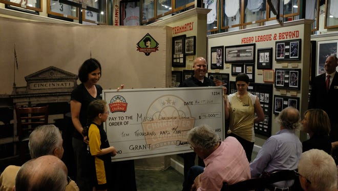 Mason Challenger League coordinator Susan Murdock (left) and league participants accept $10,000 from Character and Courage Foundation on Thursday in advance of July's Jamboree.