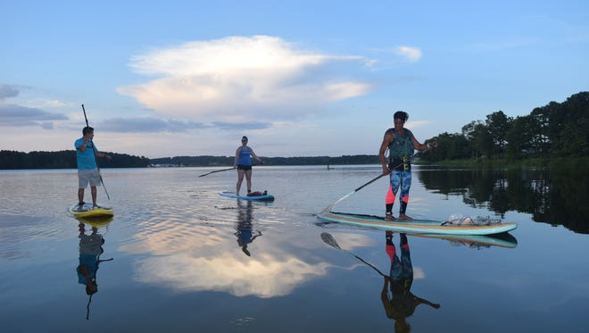 Paddleboarders enjoy a sunset paddle on lake Buhlow in Pineville.