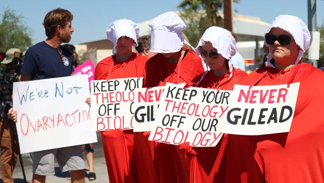 """A group of women dressed in costumes from """"The Handmaid's Tale"""" protest outside a Peoria Walgreens"""