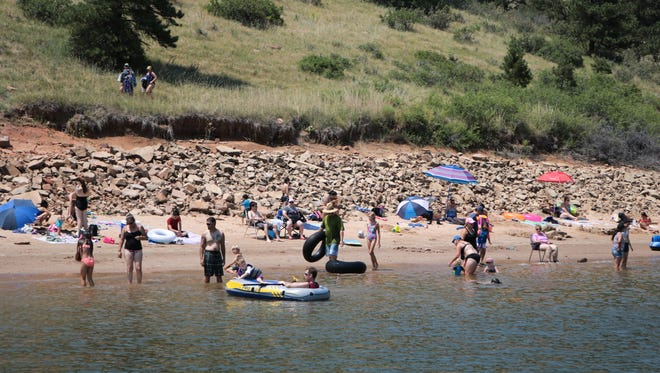 Beach goers cool off in the summer sun at South Bay swimming beach at Horsetooth Reservoir on Friday, July 6, 2018 in Fort Collins.