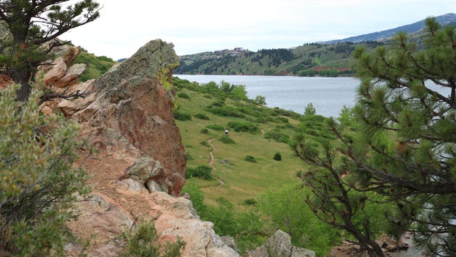 Off in the distance, a mountain biker makes his way through the trails at Horsetooth Reservoir in Fort Collins on Sunday, June 17, 2018.