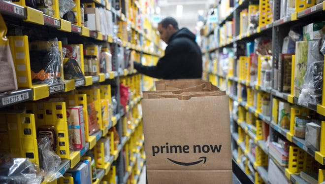 Amazon Prime Day starts at 3 p.m. July 16 but some deals for groceries are already online. In this Dec. 20, 2017, file photo, a clerk reaches to a shelf to pick an item for a customer order at the Amazon Prime warehouse in New York.