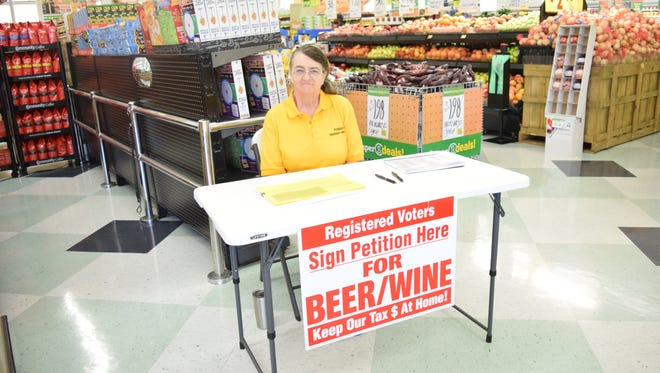 At Super 1 Foods on Highway 28 East in Pineville, Rebecca Bridges looks for registered voters to sign a petition allowing voters to potentially change alcohol laws in the city, including allowing stores to sell it.