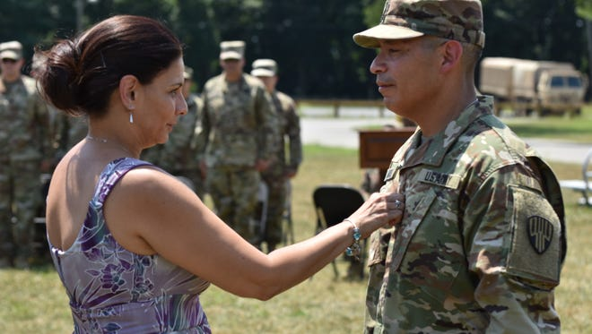 New York Army National Guard Command Sgt. Maj. Curtis Moss from the 369th Special Troops Battalion is pinned with new rank by his wife Maritza Moss, during a Change of Responsibility Ceremony on Camp Smith, Cortlandt Manor, N.Y., July 14, 2018. Moss received the promotion so he would be eligible of taking responsibility of the Battalion. (N.Y. Army National Guard photo by Spc. Andrew Valenza)