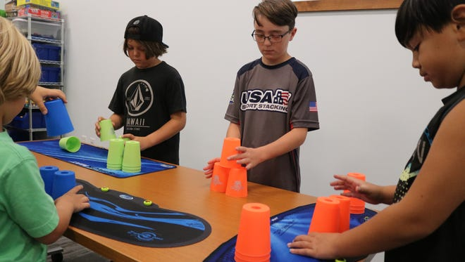 Dominic Pappagallo, center, teaches other kids the basic 3-cup pyramid in sport stacking at the Marblehead Peninsula Branch Library on Saturday.